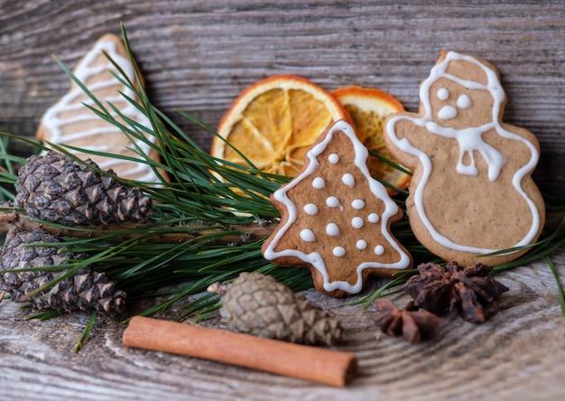 Zelfgemaakte koekjes van gekrulde gember in de vorm van een kerstboom en sneeuwpop op een houten tafel met dennentakken, kaneel, sinaasappels en dennenappels