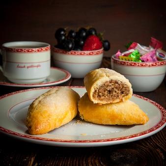 Zelfgemaakte koekjes zijaanzicht met kopje thee, snoepjes en bessen op houten tafel