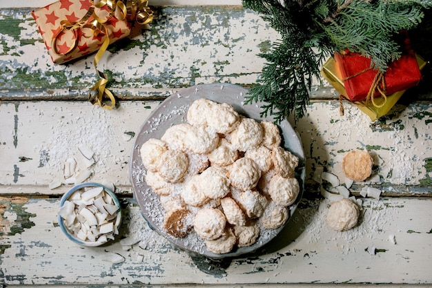 Zelfgemaakte kokosnoot glutenvrije kerstkoekjes met kokosvlokken op keramische plaat op oude houten tafel met kerstcadeaus en decoraties. plat leggen
