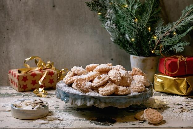 Zelfgemaakte kokosnoot glutenvrije kerstkoekjes met kokosvlokken op keramische plaat op oude houten tafel met kerstcadeaus en decoraties.