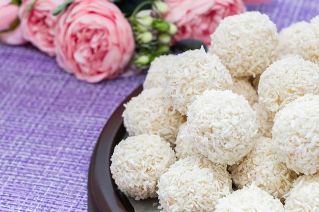 Zelfgemaakte kokosnoot snoep op een achtergrond van roze bloemen. snoepjes voor valentijnsdag.