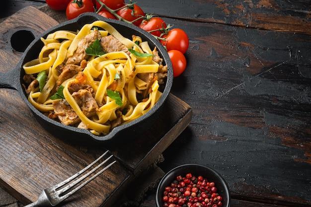 Zelfgemaakte konijn stoofpot pappardelle set, in gietijzeren pan of pot, op oude donkere houten tafel