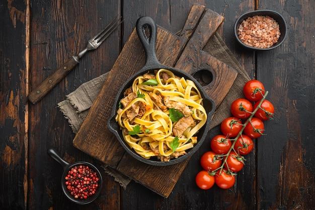 Zelfgemaakte konijnenstoofpot pappardelle set, in gietijzeren pan of pot, op oude donkere houten tafel, bovenaanzicht plat lag