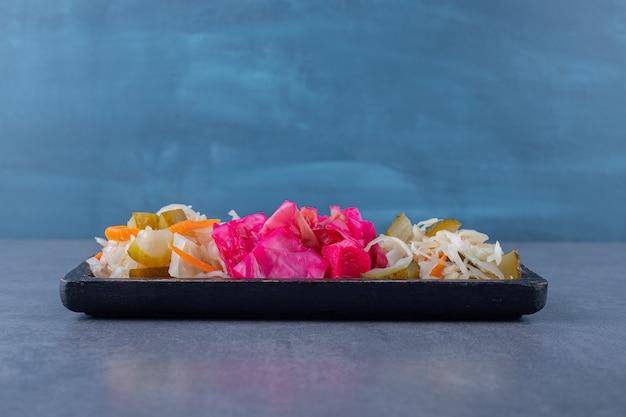 Zelfgemaakte kool augurk. gehakt en zuurkool op een houten bord.