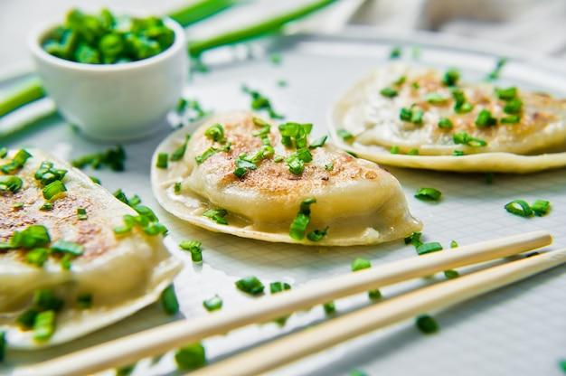 Zelfgemaakte koreaanse dumplings, eetstokjes, verse groene uien.