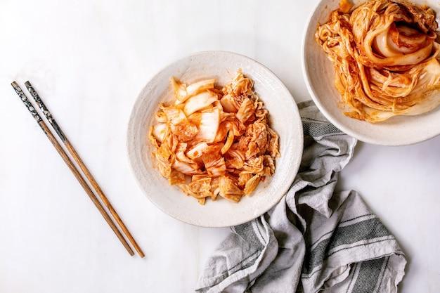 Zelfgemaakte koreaanse traditionele gefermenteerde voorgerecht kimchi kool geheel en gehakt geserveerd in keramische plaat met stokjes over witte marmeren muur. plat leggen, ruimte