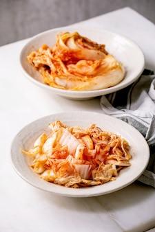 Zelfgemaakte koreaanse traditionele gefermenteerde voorgerecht kimchi kool geheel en gehakt geserveerd in keramische plaat over witte marmeren tafel.