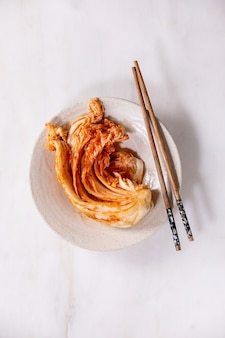 Zelfgemaakte koreaanse traditionele gefermenteerde voorgerecht kimchi kool geserveerd in keramische plaat met stokjes. plat leggen, kopie ruimte