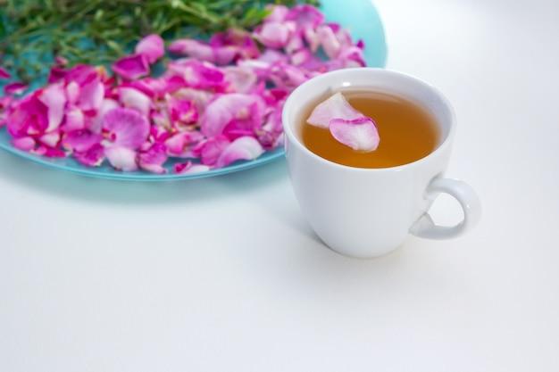 Zelfgemaakte kruidenthee in een witte kop. thee rozenblaadjes en tijm - ingrediënten voor warme gezonde drank
