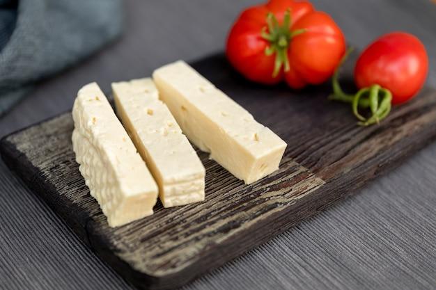 Zelfgemaakte kwark in blokjes gesneden op een vintage keukenbord een tomaat op de achtergrond