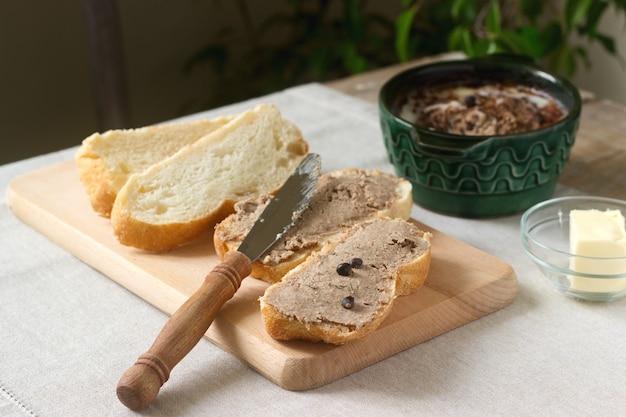Zelfgemaakte leverpastei met brood en boter. rustieke stijl.