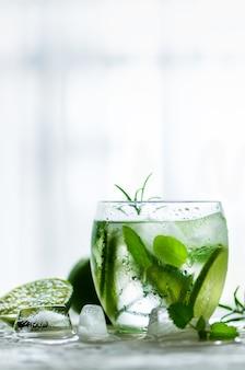 Zelfgemaakte limoenlimonade met komkommer, rozemarijn en ijs. koude drank voor hete de zomerdag.