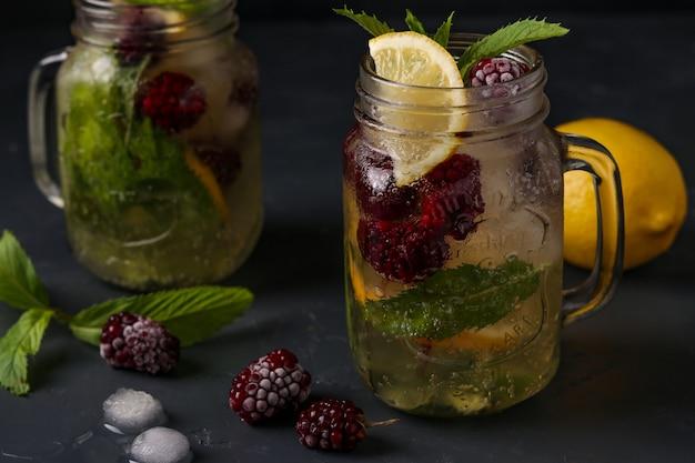 Zelfgemaakte limonade met citroen, bramen en munt in glas tegen een donkere ondergrond, horizontale foto