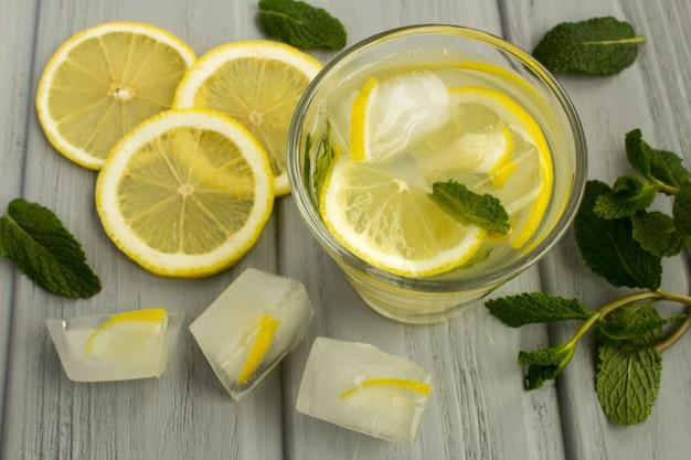 Zelfgemaakte limonade met citroen en munt op de grijze houten achtergrond. bekijk van bovenaf.
