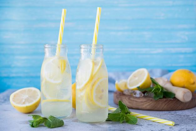 Zelfgemaakte limonade met citroenen en munt in glazen flessen