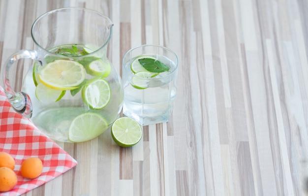 Zelfgemaakte limonade met verse citroen en munt op houten achtergrond