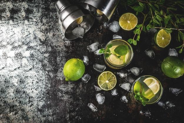 Zelfgemaakte limonade of mojito cocktail met verse limoen en muntblaadjes, donker roestig metaal, bovenaanzicht