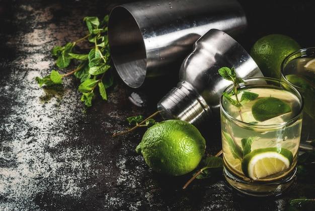 Zelfgemaakte limonade of mojito cocktail met verse limoen en muntblaadjes, donker roestig metaal,
