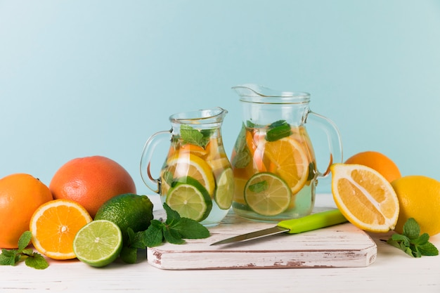 Zelfgemaakte limonadekannen met lichtblauwe achtergrond