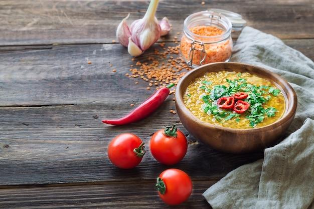 Zelfgemaakte linzensoep in kom met ingrediënten op rustieke houten achtergrond. gezond vegetarisch eten.