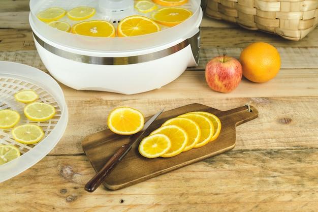 Zelfgemaakte machine om voedsel met stukjes sinaasappel op keukentafel te dehydrateren.