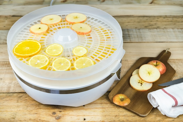 Zelfgemaakte machine om voedsel te drogen met sinaasappel- en appelschijfjes. ingeblikt voedsel.