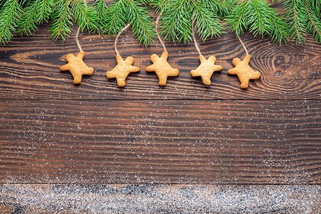 Zelfgemaakte man-vormige kerstkoekjes opknoping onder vuren takken