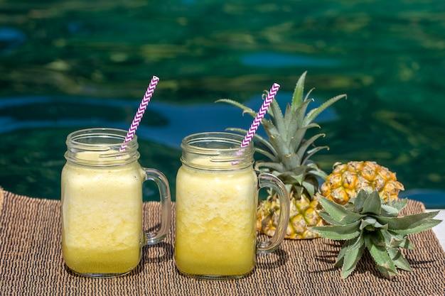 Zelfgemaakte mango en ananas smoothie gemaakt met kokosmelk in twee glazen mokken bij het zwembad