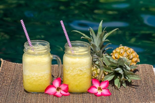 Zelfgemaakte mango en ananas smoothie gemaakt met kokosmelk in twee glazen mokken