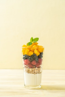 Zelfgemaakte mango, framboos en bosbes met yoghurt en granola - gezonde voeding