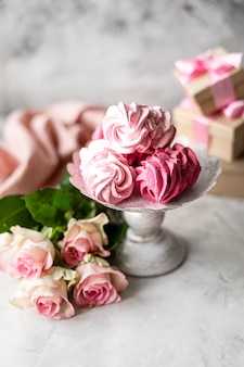 Zelfgemaakte marshmallow van bessen op een standaard en een boeket bloemen
