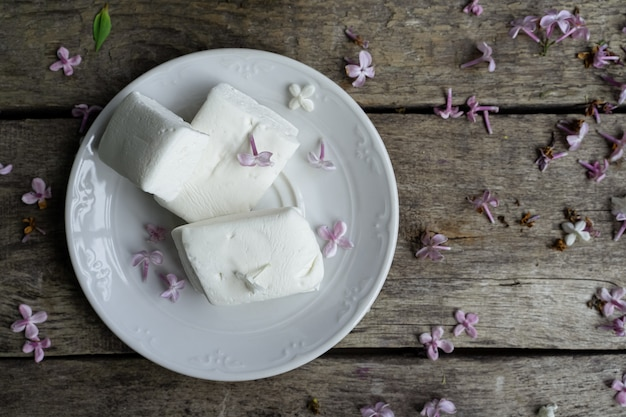 Zelfgemaakte marshmallows, lila bloemblaadjes op oude houten tafel, bovenaanzicht