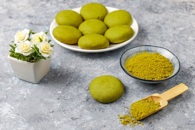 Zelfgemaakte matcha groene thee koekjes met matcha poeder op grijze betonnen tafel
