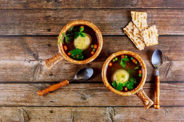 Zelfgemaakte matzo ball soep in twee potten met lepels