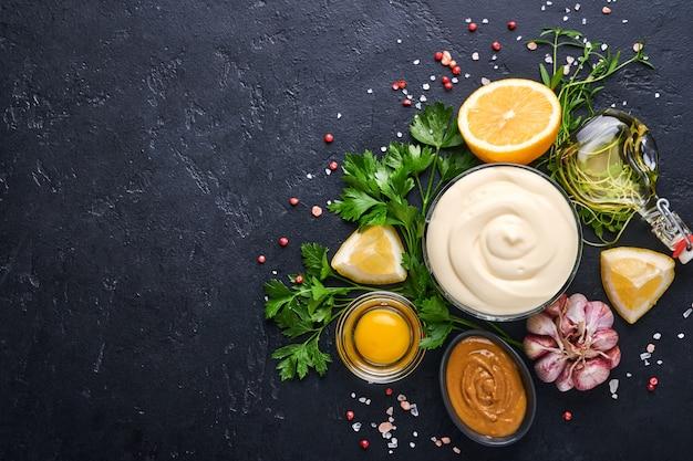 Zelfgemaakte mayonaise saus en ingrediënten citroen, eieren, olijfolie, specerijen en kruiden, zwarte achtergrond kopie ruimte. voedsel koken achtergrond. bovenaanzicht.