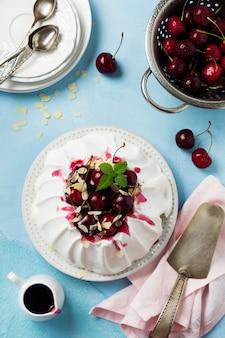 Zelfgemaakte meringue cake pavlova met slagroom, verse kersen en saus op lichte betonnen textuur oppervlak. selectieve aandacht. bovenaanzicht,