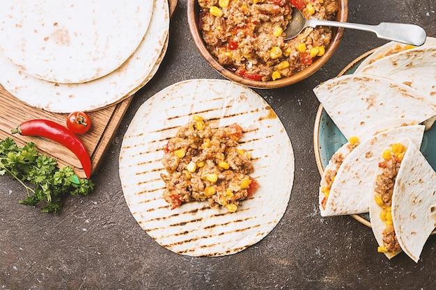 Zelfgemaakte mexicaanse fajitas van rundvlees met paprika, maïs en tortilla over donkere ondergrond, bovenaanzicht