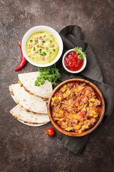 Zelfgemaakte mexicaanse fajitas van rundvlees met tortilla en guacamole en salsasauzen over zwart