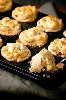 Zelfgemaakte minitaartjes van gehakt, kruimeldeeg met aardappelpuree en tijm in zwarte bakplaat. donker linnen tafelkleed, grijze muur op de achtergrond. thuis diner recept. detailopname