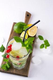 Zelfgemaakte mojito cocktail met citroen, limoen, muntblaadjes, ijs en rode bes. zomer drankje concept.