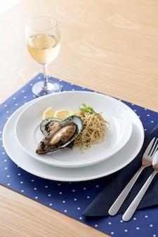 Zelfgemaakte mosselen pasta maaltijd met witte wijn op houten tafel