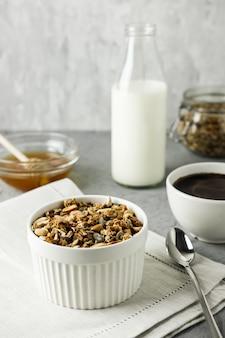 Zelfgemaakte muesli in blauwe kom met een fles melk, kopje koffie en honing.