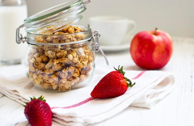 Zelfgemaakte muesli in een glazen pot. ingrediënten voor een gezond ontbijt - muesli, appel, aardbei en melk. detailopname