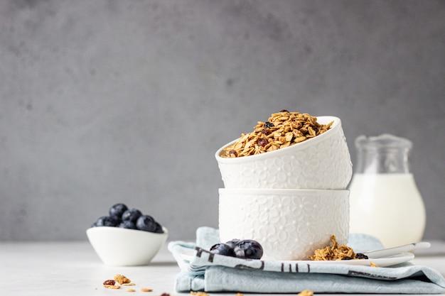 Zelfgemaakte muesli in een witte keramische kom met rozijnen, bosbessen en melk. gezonde ontbijtingrediënten