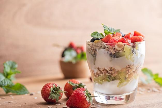 Zelfgemaakte muesli, kom havermuesli met yoghurt, verse bosbessen, moerbei, aardbeien, kiwi, munt en notenbord voor gezond ontbijt, kopieerruimte. gezond ontbijtconcept. schoon eten.
