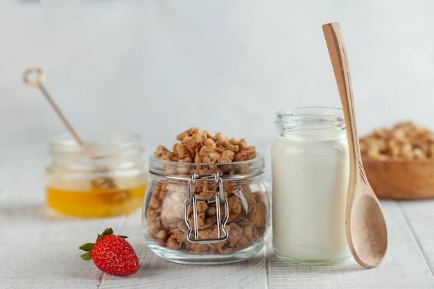 Zelfgemaakte muesli, melk in een pot, honing en aardbeien op een houten achtergrond. concept van een ontbijt, een gezond dieet.