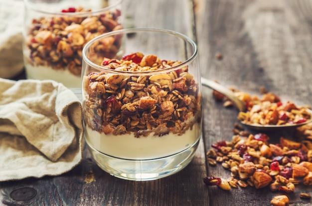 Zelfgemaakte muesli met noten en gedroogde veenbessen en yoghurt in glazen op rustieke houten achtergrond