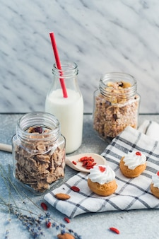 Zelfgemaakte muesli; muesli; cake met muffins; droge vruchten; melk met rode stro en doek op concrete achtergrond