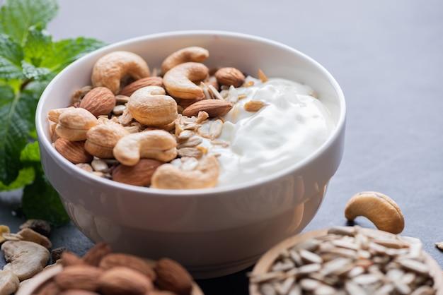 Zelfgemaakte muesli of muesli, kom haver muesli met yoghurt, amandel, cashewnoten, munt en noten op het zwarte rotsbord voor gezond ontbijt, kopieer ruimte. gezond ontbijtmenuconcept.