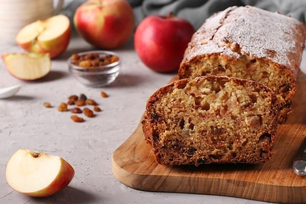 Zelfgemaakte muffin met appels en rozijnen op een houten bord op een grijze achtergrond, close-up, kopie ruimte